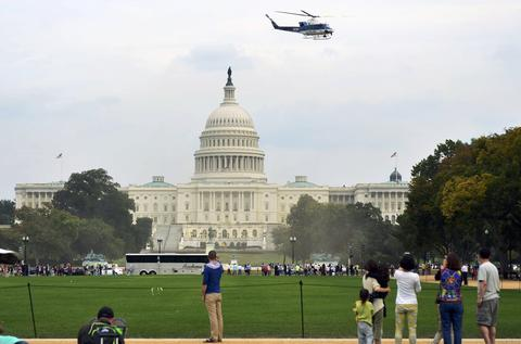 Tourists watch from the U.S. national mall as a Park Police helicopter flies past the Capitol dome evacuating an injured U.S Capitol police officer from the scene of a shooting on Capitol Hill in Washington, October 3, 2013. The U.S. Capitol was locked down briefly on Thursday after gunshots were fired outside the building following a car chase across central Washington and a number of people including a law enforcement officer were hurt, officials said.