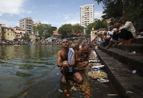 "Hindu devotees perform prayers on the steps of a holy pond on the auspicious day of ""Mahalaya"" in Mumbai October 4, 2013. Hindus offer prayers with holy water after taking a dip in the river to honour the souls of their departed ancestors during Mahalaya, which is also called 'Shraadh' or Pitra Paksha."
