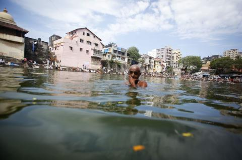 "A Hindu devotee takes a dip in a holy pond on the auspicious day of ""Mahalaya"" in Mumbai October 4, 2013. Hindus offer prayers with holy water after taking a dip in the river to honour the souls of their departed ancestors during Mahalaya, which is also called 'Shraadh' or Pitra Paksha."