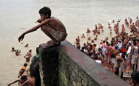 "A Hindu boy brushes his teeth with a neem twig as others take a dip on the banks of the Ganges river on the holy day of ""Mahalaya"" in Kolkata October 4, 2013. Hindus offer prayers with holy water after taking a dip in the river to honour the souls of their departed ancestors during Mahalaya, which is also called 'Shraadh' or Pitra Paksha."