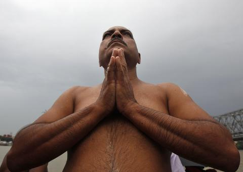 "A Hindu man offers prayers on the banks of the Ganges river on the holy day of ""Mahalaya"" in Kolkata October 4, 2013. Hindus offer prayers with holy water after taking a dip in the river to honour the souls of their departed ancestors during Mahalaya, which is also called 'Shraadh' or Pitra Paksha."
