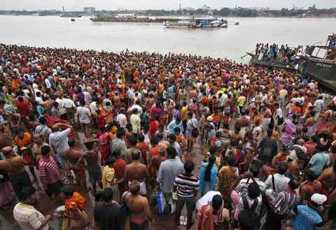 "Hindu devotees gather to perform prayers on the banks of the Ganges river on the holy day of ""Mahalaya"" in Kolkata October 4, 2013. Hindus offer prayers with holy water after taking a dip in the river to honour the souls of their departed ancestors during Mahalaya, which is also called 'Shraadh' or Pitra Paksha."