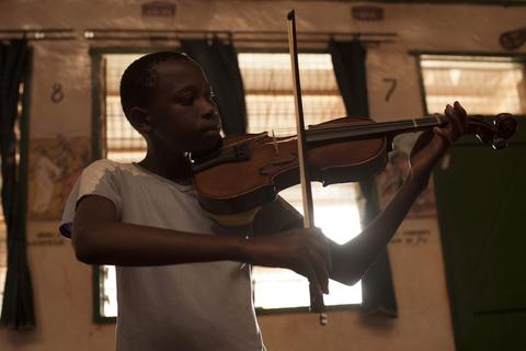 Steven Kamau, 13, learns how to play a violin during a class held as part of a programme by the Orchestra of Ghetto Classics in the Korogocho slum of Nairobi October 6, 2013. The orchestra, in partnership with the Art of Music Foundation and the St. John's Catholic Church, started the project with the aims of teaching music to the children and youths living in the slum and providing them with income opportunities from the skills they learn.