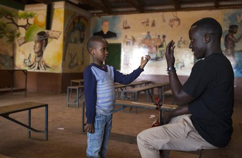 Samuel Njoroge (L), 7, learns how to hold a violin during a class held as part of a programme by the Orchestra of Ghetto Classics in the Korogocho slum of Nairobi October 6, 2013. The orchestra, in partnership with the Art of Music Foundation and the St. John's Catholic Church, started the project with the aims of teaching music to the children and youths living in the slum and providing them with income opportunities from the skills they learn.
