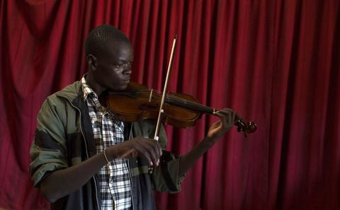 A man plays a violin during a class held as part of a programme by the Orchestra of Ghetto Classics in the Korogocho slum of Nairobi October 6, 2013. The orchestra, in partnership with the Art of Music Foundation and the St. John's Catholic Church, started the project with the aims of teaching music to the youths living in the slum and providing them with income opportunities from the skills they learn.