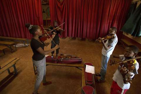 Music teacher Etta Madet (L) conducts a violin class with youths as part of a programme by the Orchestra of Ghetto Classics held in the Korogocho slum of Nairobi October 6, 2013. The orchestra, in partnership with the Art of Music Foundation and the St. John's Catholic Church, started the project with the aims of teaching music to the youths living in the slum and providing them with income opportunities from the skills they learn.
