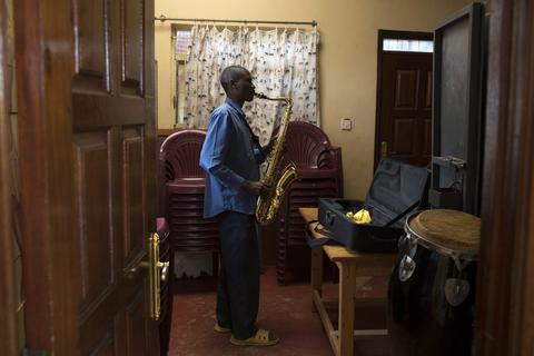 A man plays a tenor saxophone during a training session held as part of a programme by the Orchestra of Ghetto Classics in the Korogocho slum of Nairobi October 6, 2013. The orchestra, in partnership with the Art of Music Foundation and the St. John's Catholic Church, started the project with the aims of teaching music to the youths living in the slum and providing them with income opportunities from the skills they learn.