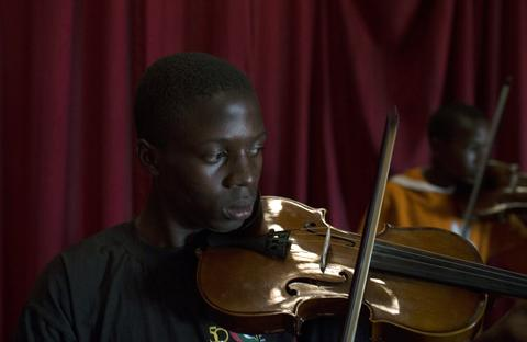 Youths attend a violin class held as part of a programme by the Orchestra of Ghetto Classics in the Korogocho slum of Nairobi October 6, 2013. The orchestra, in partnership with the Art of Music Foundation and the St. John's Catholic Church, started the project with the aims of teaching music to the youths living in the slum and providing them with income opportunities from the skills they learn.