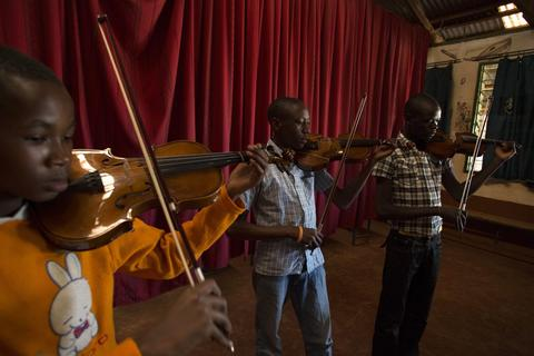 Youths play the violin during a class held as part of a programme by the Orchestra of Ghetto Classics in the Korogocho slum of Nairobi October 6, 2013. The orchestra, in partnership with the Art of Music Foundation and the St. John's Catholic Church, started the project with the aims of teaching music to the youths living in the slum and providing them with income opportunities from the skills they learn.