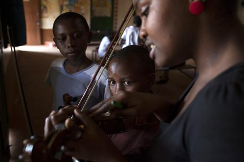 Children listen as music teacher Etta Madet conducts a violin class as part of a programme by the Orchestra of Ghetto Classics held in the Korogocho slum of Nairobi October 6, 2013. The orchestra, in partnership with the Art of Music Foundation and the St. John's Catholic Church, started the project with the aims of teaching music to the children and youths living in the slum and providing them with income opportunities from the skills they learn.