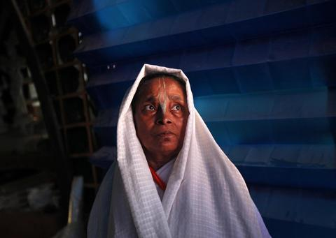 A widow stands inside a marquee where an idol of Hindu goddess Durga is i
