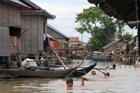 Cambodian children swim in flood waters at a village in Kandal province on October 7, 2013. More than 80 people in Cambodia have died in recent floods caused by heavy rains and the Mekong River overflowing its banks, an official said on October 7, 2013.