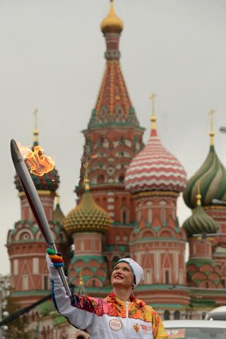 Three-time world champion and two-time Olympic champion in gymnastics, Svetlana Khorkina, holds the Olympic torch in front of St.Basil's cathedral just outside the Red Square in Moscow, on October 7, 2013, during a ceremony to kick off the Sochi 2014 Winter Olympic torch relay across Russia.