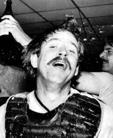 Rick Dempsey is showered with champagne by teammates.