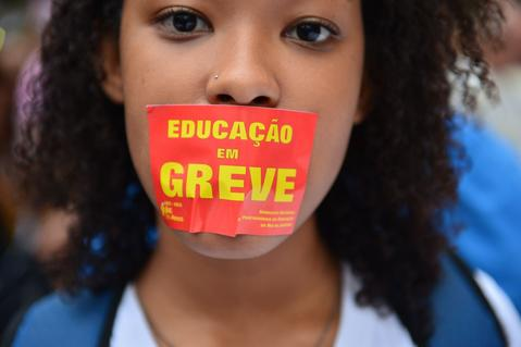 "A girl bears a sticker in her mouth reading ""Education on strike"" during a teachers protest demanding better working conditions and against police beating, on October 7, 2013 in Rio de Janeiro."