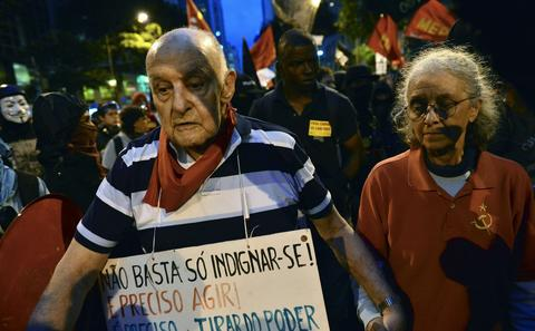 An elderly couple walks during a teachers protest demanding better working conditions and against police beating, on October 7, 2013 in Rio de Janeiro.