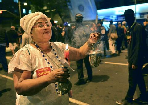 A woman waves an incense burner during a teachers protest demanding better working conditions and against police beating, on October 7, 2013 in Rio de Janeiro.