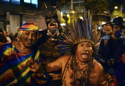 A Brazilian native and demonstrators in fancy dress shout slogans during a teachers protest demanding better working conditions and against police beating, on October 7, 2013 in Rio de Janeiro.