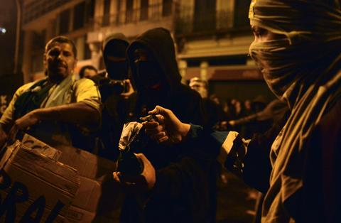 Masked demonstrators prepare to light a molotov cocktail during a teachers protest demanding better working conditions and against police beating, on October 7, 2013 in Rio de Janeiro. AFP PHOTO / CHRISTOPHE SIMONCHRISTOPHE SIMON/AFP/Getty Images ORG XMIT: