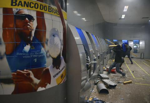 A group of masked demonstrators destroy cash dispensers, following a peaceful teachers protest demanding better working conditions and against police beating, on October 7, 2013 in Rio de Janeiro.