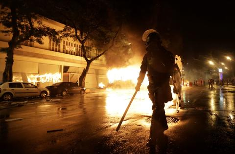A riot policeman walks in front of a burning bus after demonstrators from the group Black Bloc set fire to it during protest in Rio de Janeiro October 7, 2013. The protest is to demand changes in the public state and municipal education system.