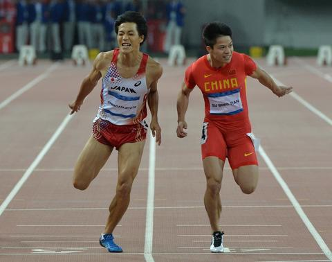 Su Bingtian of China (R) crosses the finish line beside second place Ryota Yamagata of Japan to win the Men's 100m Final at the East Asian Games held at the Tianjin Olympic Center Stadium in Tianjin on October 8, 2013.  The East Asian Games which are held every four years see nine countries including China, Japan, South and North Korea participating in 262 events in 22 different sports.