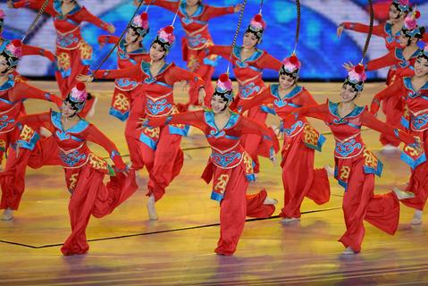 Chinese performers dance during the opening ceremony of the East Asian Games at a gymnasium in Tianjin on October 6, 2013. More than 2,400 athletes from nine countries are set to take part in the multi-sport event in the harbour city of Tianjin, competing in 24 different sports.