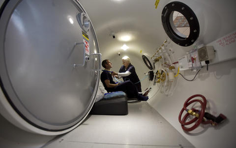 "Sarah Stoltman fits the bottom of a ""hyperbaric hood"" around Jim's neck as he sits in a hyperbaric chamber at Renova Wellness Center in Norfolk on August 13.  For a span of several weeks, Jim receives daily 70-minute oxygen therapy treatments in the hyperbaric chamber."