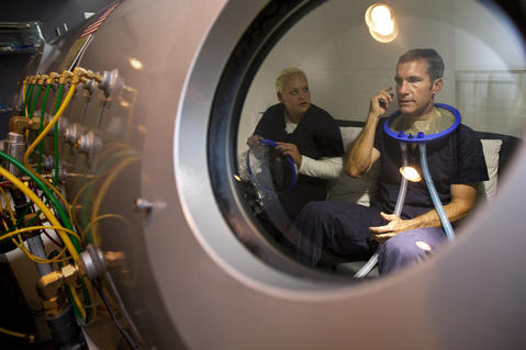 Sarah Stoltman talks with Jim while sitting in a hyperbaric chamber at Renova Wellness Center in Norfolk on August 13. For a span of several weeks, Jim receives daily 70-minute oxygen therapy treatments in the hyperbaric chamber.
