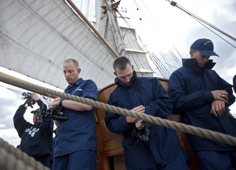 Officer candidates check the time before using sextants to determine the position of the Coast Guard Barque Eagle as the moon rises on Tuesday evening.