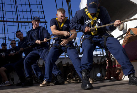 "Boatswain's Mate ""A"" School student Joshua Coffield (center) helps to raise the topsail of the Coast Guard Barque Eagle on Tuesday afternoon."