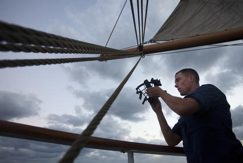Officer Candidate Paul Larouche uses a sextant to determine the position of the Coast Guard Barque Eagle as the moon rises on Tuesday evening.