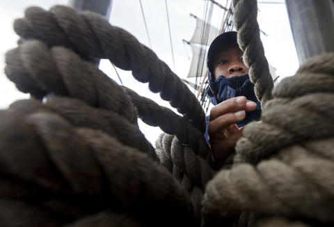 Ensign Trish Ephraim makes up the lines after helping to raise the sails of the Coast Guard Barque Eagle on a rainy Tuesday morning.