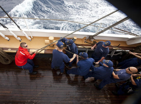 Crew members and trainees pull a line tight on the Coast Guard Barque Eagle against strong winds and surf on Tuesday.