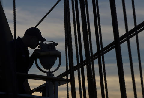 A Coast Guard trainee keeps a lookout from the Coast Guard Barque Eagle as the sun sets on Sunday evening.