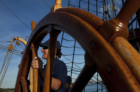 Officer Candidate Catherine Lawson, of Gloucester, helps to steer the Coast Guard Barque Eagle as it heads to sea early Sunday afternoon.