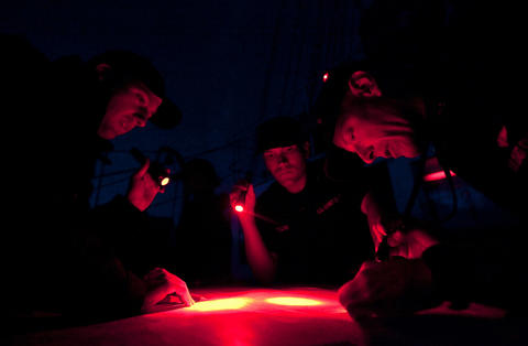 Crew members and trainees use lights to plot the course of the Coast Guard Barque Eagle on Sunday evening.