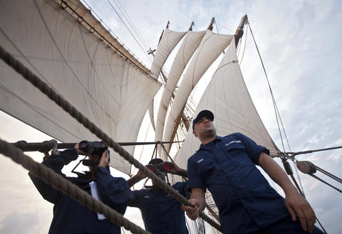 "(From left) Seaman Lawren Hill-Hand and Boatswain's Mate ""A"" School students Joseph Brock and Carlos Tobon keep a lookout from the Coast Guard Barque Eagle early Monday evening."