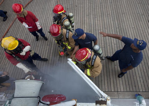 Crew members direct Coast Guard officer candidates as smoke pours out of the laundry room during a fire drill aboard the Coast Guard Barque Eagle on Monday afternoon.