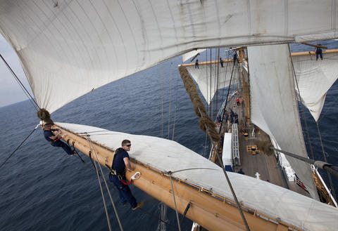 Chief Warrant Officer 3 Pete Clark and Officer Candidate Thomas McGuire work on the yard to set the upper sail of the Coast Guard Barque Eagle on Monday afternoon.