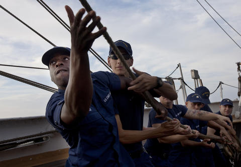 "Students from the Boatswain's Mate ""A"" School pull a line to raise the course of the Coast Guard Barque Eagle on Monday."