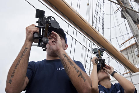 "Robert Falato (left), a student at the Boatswain's Mate ""A"" School, uses a sextant to find the position of the sun on the Coast Guard Barque Eagle on Monday."