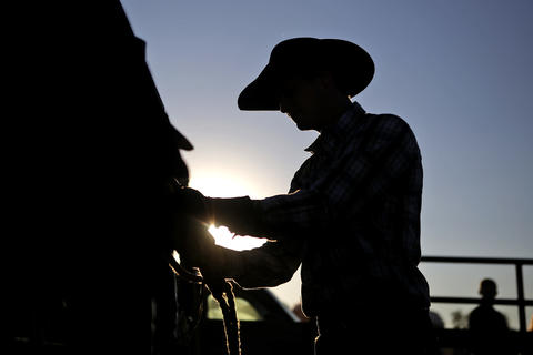 Travis Finley of Jacksonville, North Carolina prepares his rope prior to the start of Saturday's bull riding competition at the Isle of Wight County Fair. Twelve riders competed Saturday evening in an attempt to ride a bull for eight seconds.