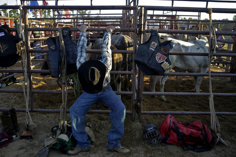 Travis Finley of Jacksonville, North Carolina stretches prior to the start of Saturday's bull riding competition at the Isle of Wight County Fair. Twelve riders competed Saturday evening in an attempt to ride a bull for eight seconds.