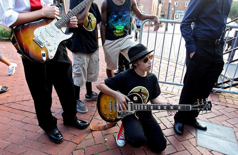Zachary Salsberry warms up his guitar as the Blues Kids prepare to take the stage one last time at the Hampton Block Party.