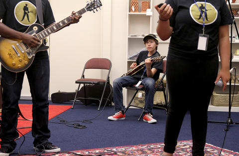 Zachary Salsberry waits his turn to play during a blues camp rehearsal  at the American Theater.
