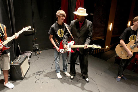 Blues Camp instructor Fernando Jones demonstrates a guitar technique to Joey Nobel during a rehearsal session at the American Theater.