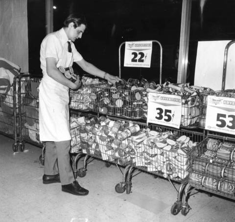 Night stock man Alex Miladinovich loads sales items into a basket in Dominicks Food Store at 6009 N. Broadway on June 15, 1972.