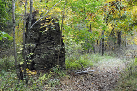 A stone chimney sits along the trail.