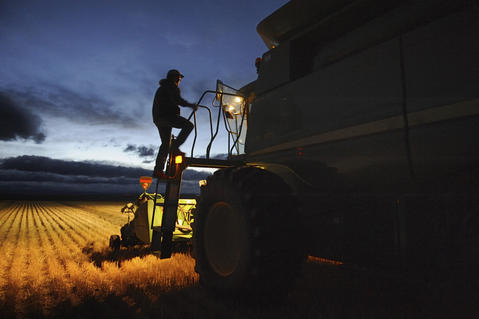 Lloyd Giles climbs up onto his combine to relieve his wife, Tara, who had been driving the afternoon shift during the annual harvest on September